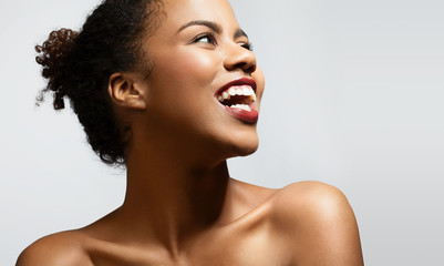 Happy black woman with bare shoulders on a white background
