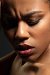 Close-up face of a sad black girl on black background