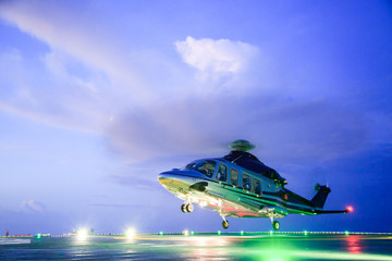 Stores photo Hélicoptère helicopter parking landing on offshore platform. Helicopter transfer crews or passenger to work in offshore oil and gas industry.Night flight training of Pilot and coordinate pilot.