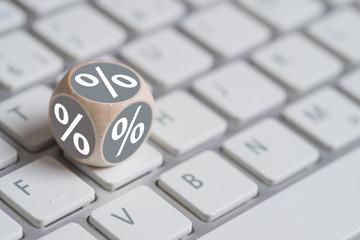 Würfel mit Prozentzeichen auf Tastatur