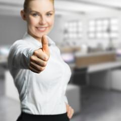 junge Geschftsfrau mit Top-Daumen vor Bürohintergrund