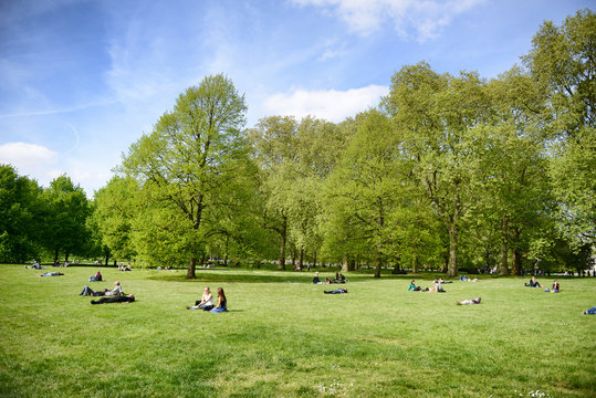 People lying on grass relaxing in a London Park
