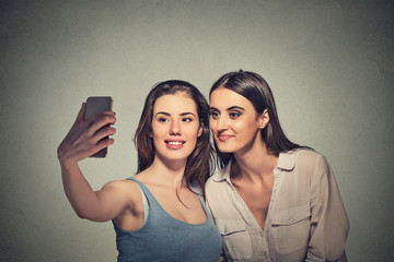 Two beautiful girls taking selfie with smart phone camera