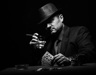 Male gambler playing poker and smokes a cigar, Black and white