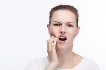 Junge hübsche Frau hält sich die Wange vor Zahnschmerzen