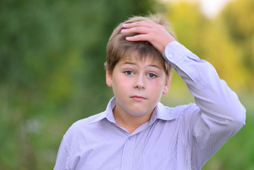 Astonished boy holding his hands behind  head