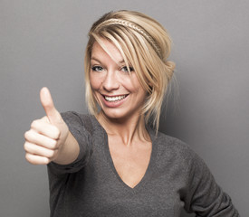 agreement concept - excited young woman with trendy blonde hair giving a thumb up for satisfaction