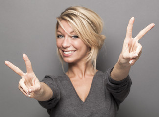 satisfaction concept - sign of double victory in the foreground for excited young woman with trendy blonde hair