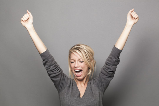 shouting 20s blonde woman raising hands for victory