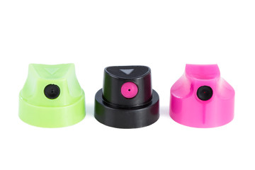 Close-up of three clean colorful spray can nozzles in a row, isolated on white background.