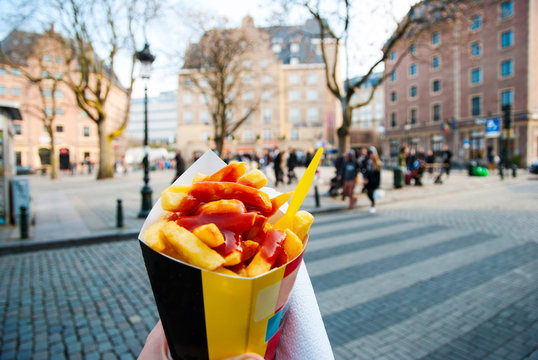 Holding typical belgian fries in hand in Brussels