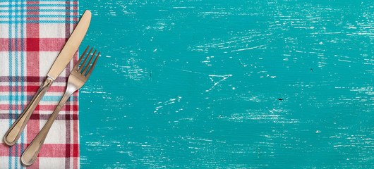 Fork and knife on napkin on turquoise wood