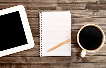 Notepad with tablet and cup of coffee