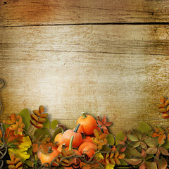 Pumpkins and autumn leaves on the wooden background