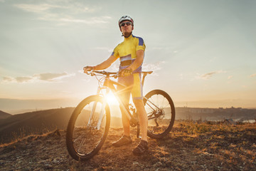 low angle view of cyclist standing with mountain bike on trail a