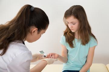 Doctor Measuring Blood Sugar Level Of Girl