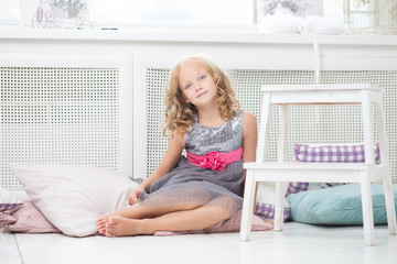 Young girl sitting on the floor of her room