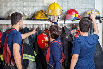Firefighters Removing Helmets From Shelf