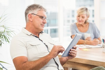 Serious businessman scrolling on a tablet