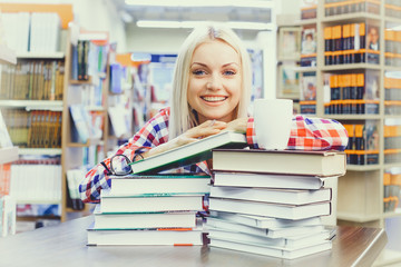 Portrait of young blonde girl studying in library