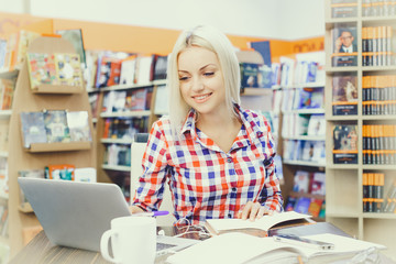Girl studying on laptop in library