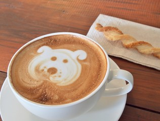 """Latte Coffee art """"Dog Face"""" and biscuit stick on the wooden desk."""