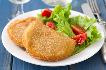 portuguese meat cookies with fresh salad on white dish on blue background
