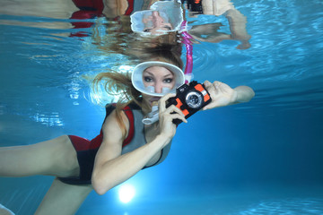 Sexy female snorkeler with neoprene swimsuit and underwater camera