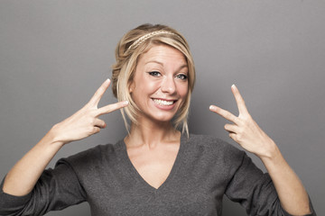 satisfaction concept - excited young woman with trendy blonde hair making the sign of victory twice for agreement