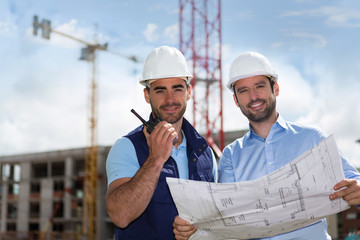 Engineer and worker watching blueprint on construction site