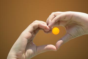 Girl hand in heart form love on sunset sky