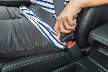 Young man fastening seat belt in the car