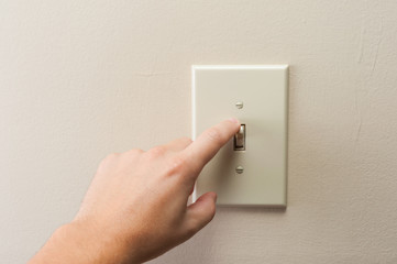 Hand turning wall light switch off. color image in horizontal orientation