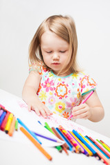 Little girl drawing with colourful pencils.