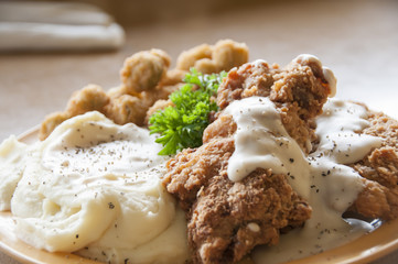 Chicken fried steak with mashed potatoes and country gravy with fried okra.