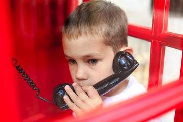 call emergency services. alarmed by the boy speaks by phone from a phone booth
