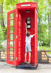 boy in a phone booth. the child reaches for the tube in a telephone box in british style