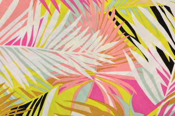 Colorful tropical leaves pattern on fabric. Pink, yellow and white palm leaves print as background. Wall mural