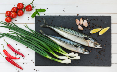 Fresh mackerel fish on a slate cutting board. Top view