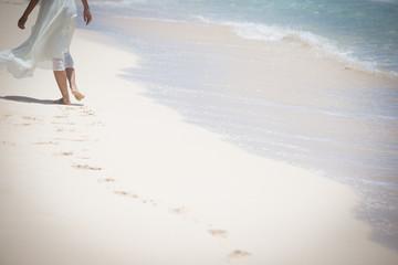 海辺を歩く女性の足とあしあと