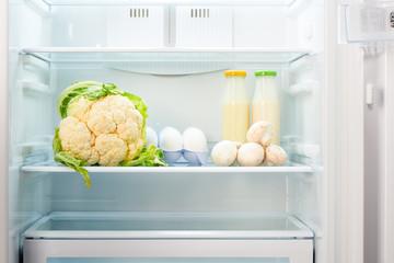 Cauliflower, white eggs, champignon mushrooms and two glass bottles of yoghurt on shelf of open empty refrigerator. Weight loss diet concept.