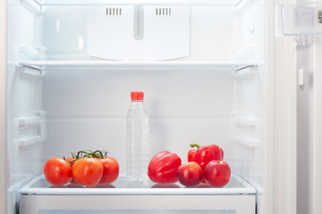 Branch of red tomatoes, two red peppers, two two-colored orange and red peaches and a bottle of water on shelf of open empty refrigerator. Weight loss diet concept.