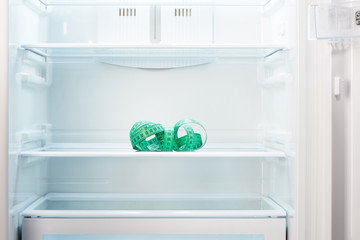 Green measuring tape on shelf of open empty refrigerator. Weight loss diet concept.