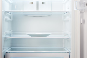 Empty white plate in open empty refrigerator. Weight loss diet concept.