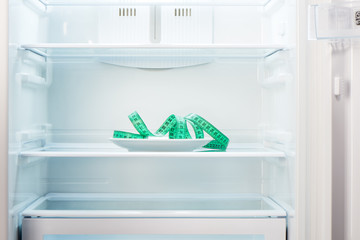 Green measuring tape on white plate in open empty refrigerator. Weight loss diet concept.
