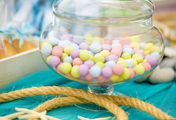 Still life, holidays concept. Colorful sweet candies in a bowl and ropes. Selective focus.