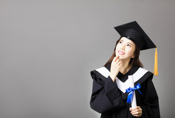 beautiful young  graduate holding diploma and thinking