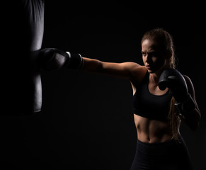 young beautiful blonde girl in boxing gloves pushes the bag