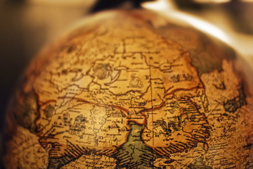 Close up of old vintage globe with old handmade map soft colors