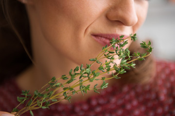 Closeup of fresh thyme being smelled by an elegant woman